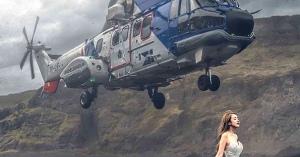 結婚写真の撮影中にヘリコプターが突然花嫁の上に飛来した予想外のスナップショット。