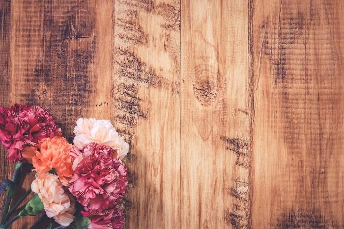 古材の床に置かれたカーネーションの花|フリー写真画像