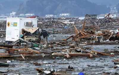 津波で流されたトラック内を確認するドライバー