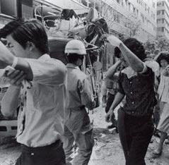 けがをして病院に向かう人々。左手前が三菱重工ビル