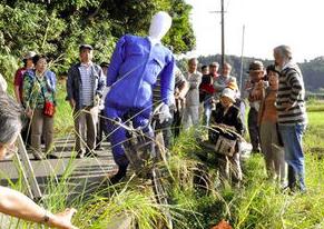 「大崎事件」の現場周辺で、人形を使って調査する原口アヤ子さんの支援者ら