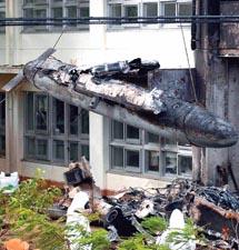 墜落したヘリコプターの一部をクレーンでつり上げ、回収する米軍関係者。後ろはヘリが衝突した本館
