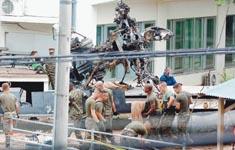 ローター部分とみられる残骸を撤収する米兵ら
