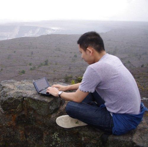 ものすごいところでものすごい小さいノーパソでタイピングに勤しむ隅野貴裕氏