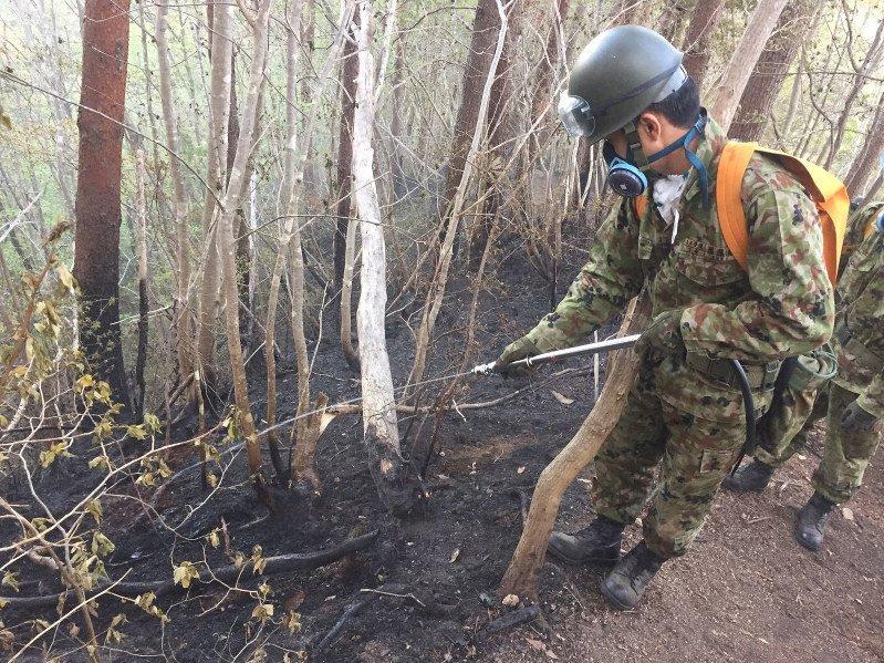 くすぶる山林に放水する自衛隊員。