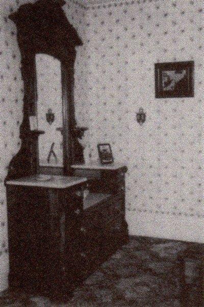 妻アビー・ボーデンは、この鏡の前でアンドリュー同様、 頭を叩き割られて血まみれになって倒れていた。 壁にかけてあるのは事件当時の現場写真。