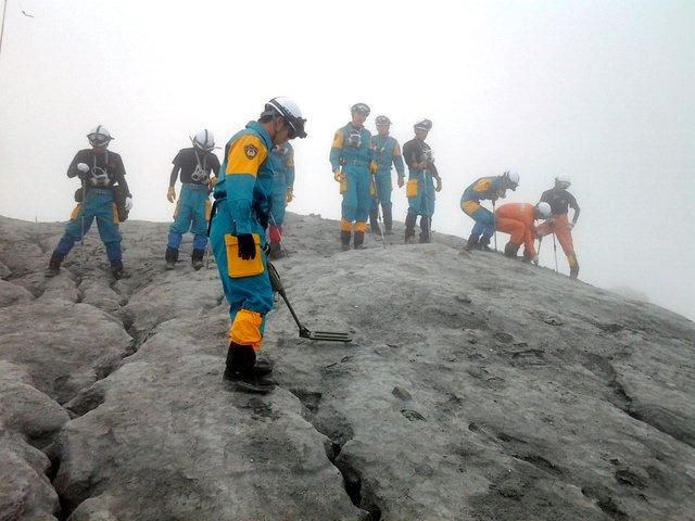 再捜索初日、もやがかかる中、火山灰をスコップで掘り起こし、行方不明者の手がかりを探す岐阜県の捜索隊