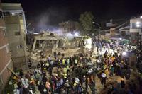 19日、地震で倒壊した学校で救助作業をする大勢の人たち=メキシコ市(AP